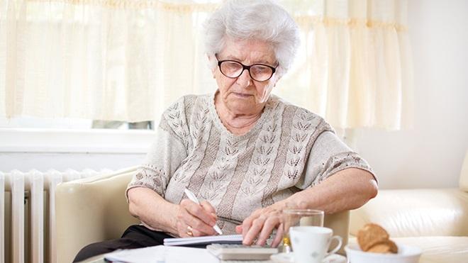 idosa reformada sentada no sofá a escrever