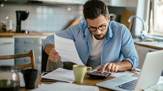 homem a tratar do pagamento de impostos em frente a um computador