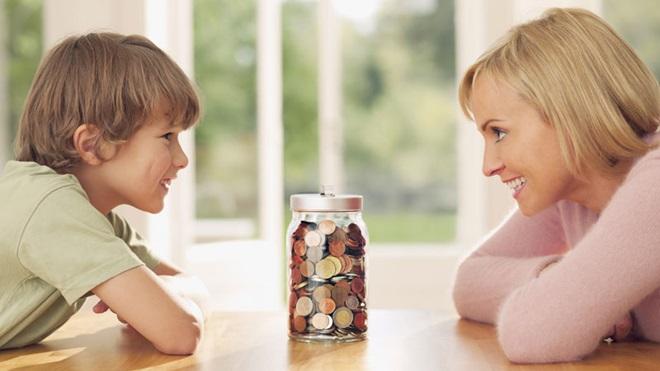 Mãe e filho a olhar para frasco com moedas poupadas