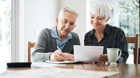 Casal idoso faz contas num papel