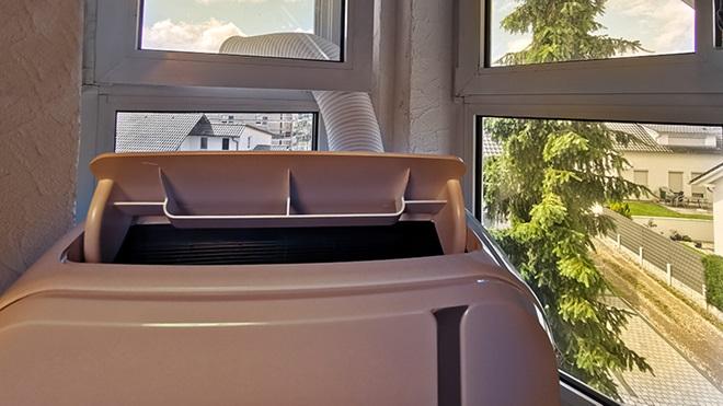 Aparelho de ar condicionado portátil junto a uma janela e com o tubo preso naquela