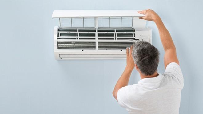 Homem a abrir um aparelho de ar condicionado que está numa parede