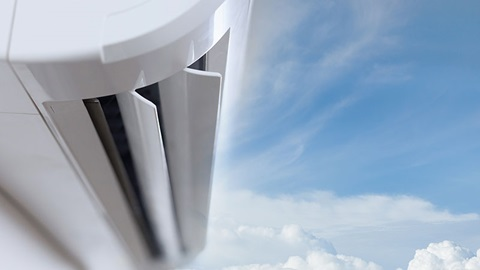 Detalhe de uma unidade interior de um aparelho de ar condicionado, com um céu azul com nuvens como pano de fundo.