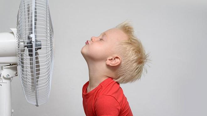 criança à frente de uma ventoinha