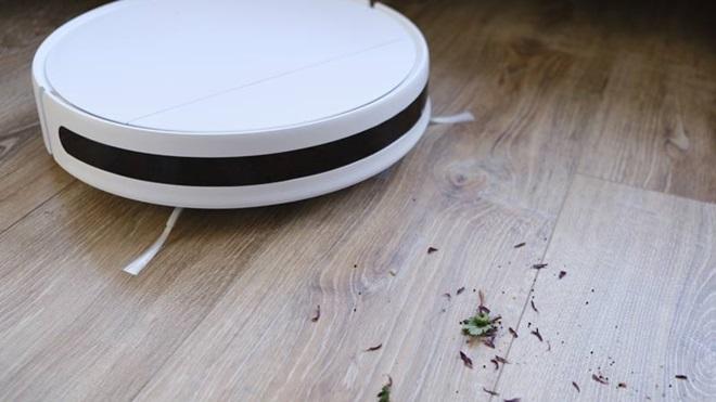 Aspirador robô branco a limpar restos de terra e folhas num soalho de madeira