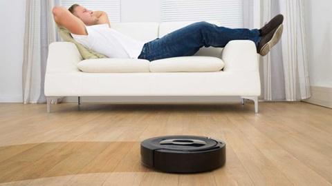 Em primeiro plano, um aspirador robô preto deixa um rasto limpo sobre um chão empoeirado. Ao fundo, um rapaz descansa, com as mãos repousadas atrás da cabeça, estendido num sofá branco.
