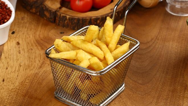 pequeno cesto de alumínio com batatas fritas numa mesa