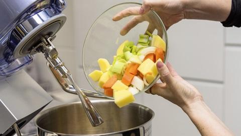 Plano de pormenor da parte superior de um robô de cozinha, com a tampa aberta, levantada. Do lado direito da imagem, um par de mãos agarra uma taça transparente contendo alguma fruta cortada, que se prepara para despejar para dentro do copo do robô.