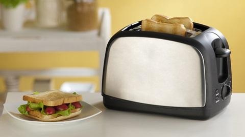 Em primeiro plano, sobre uma mesa, uma torradeira de cor preta e prateada exibe duas fatias de pão torradas e é ladeada por um prato com uma sanduíche de pão torrado, alface e tomate.