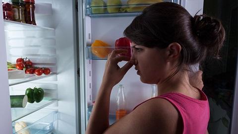 pessoa confrontada com mau cheiro do frigorífico quando abre a porta