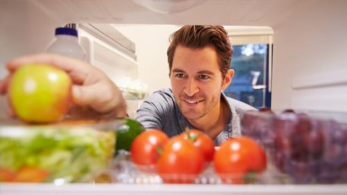 homem a tirar um tomate do frigorífico