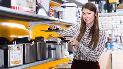 Senhora junto a uma prateleira com fritadeiras elétricas, numa loja
