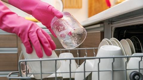 Mãos com luvas de borracha cor de rosa a pôr um copo dentro da máquina de lavar loiça