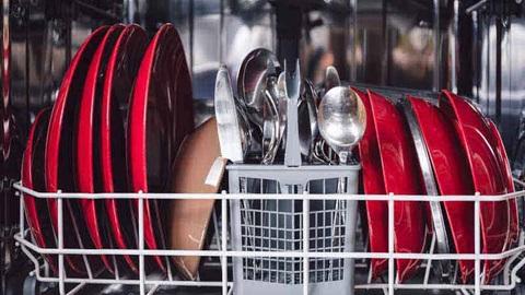 Talheres e pratos vermelhos dentro da máquina de lavar loiça.