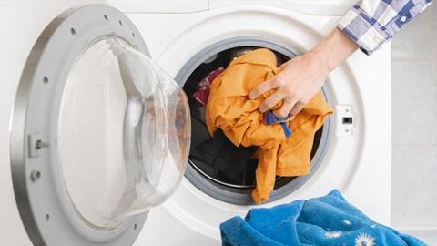 Mão a colocar peças de roupa colorida dentro do tambor da máquina de lavar roupa.