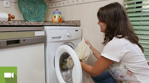 Na cozinha, uma senhora retira roupa da máquina de lavar
