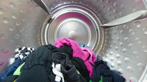 Roupa colorida dentro do tambor da máquina de secar roupa.