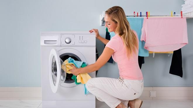Mulher sorridentes de calças brancas e t-shirt cor de rosa coloca roupa dentro da máquina de secar.