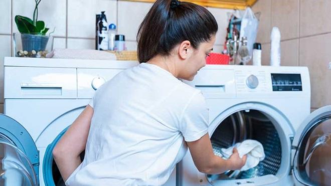 mulher a colocar roupa dentro de máquina de secar roupa