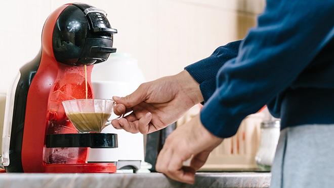 homem em casa a tirar café da máquina