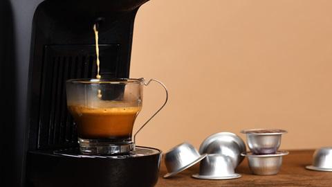 Chávena transparente debaixo de uma máquina de café de cápsulas