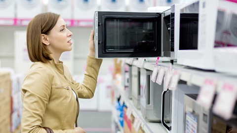 Mulher abre porta de microondas numa loja para ver o seu interior enquanto escolhe que modelo comprar