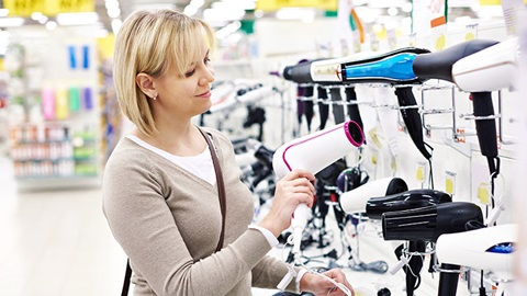 Mulher loira no supermercado a escolher secador de cabelo