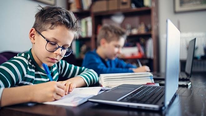 Dois rapazes sentados a uma mesa, em casa, escrevem num caderno e têm um computador aberto à sua frente