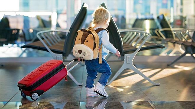 criança a empurrar trólei de viagem no aeroporto