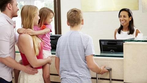 Pais e filhos a fazerem check-in no hotel
