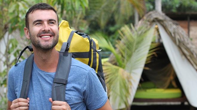 homem de mochila às costas com tenda por trás