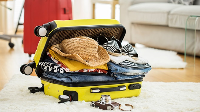 mala de viagem amarela cheia de roupa deitada no chão em cima de tapete pérola