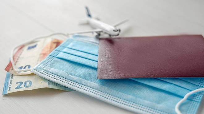 notas, máscara cirúrgica, passaporte e avião em miniatura sobrepostos