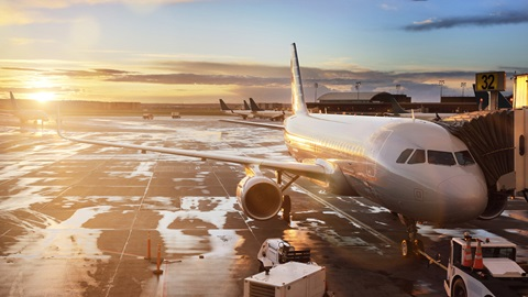 Um avião parado, com ligação a uma manga e cercado por carrinhos de apoio, encontra-se parado num pavimento de alcatrão ainda com algumas poças de água por secar. Ao fundo, um céu com algumas nuvens dispersas e o sol baixo.