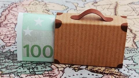mala de viagem, em cima de um mapa, e com uma nota de 100 euros por perto