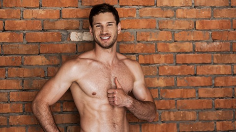 homem em tronco nu na rua sorridente em frente a uma parede de tijolos