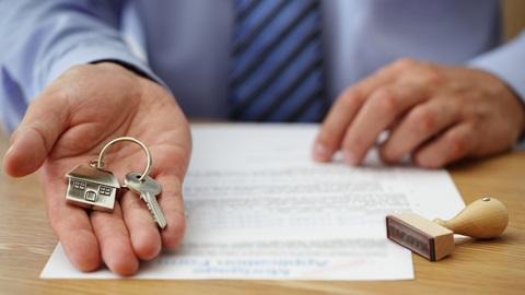 homem entrega chave de uma casa com a mão direita enquanto lê testamento relativo a herança