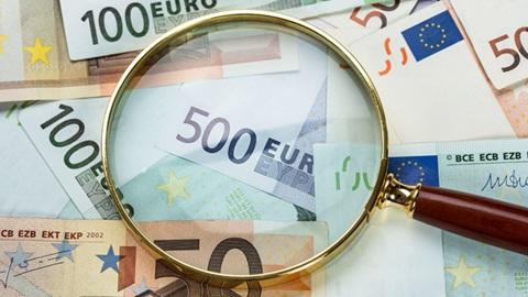 lupa em cima de notas de 500, 100 e 50 euros