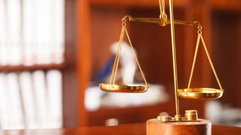 pequena balança dourada, a simbolizar a justiça, em cima de uma mesa com estantes atrás