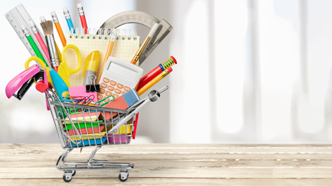 carrinho de compras em miniatura carregado de materiais escolares