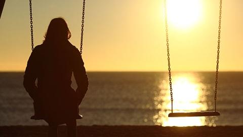 mulher no baloiço ao pôr-do-sol