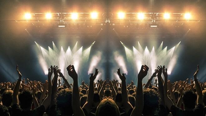 pessoas de mãos no ar a assistir a um concerto