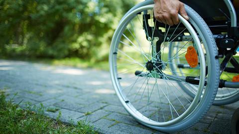 pormenor da roda de uma cadeira de rodas na qual circula uma pessoa deficiente