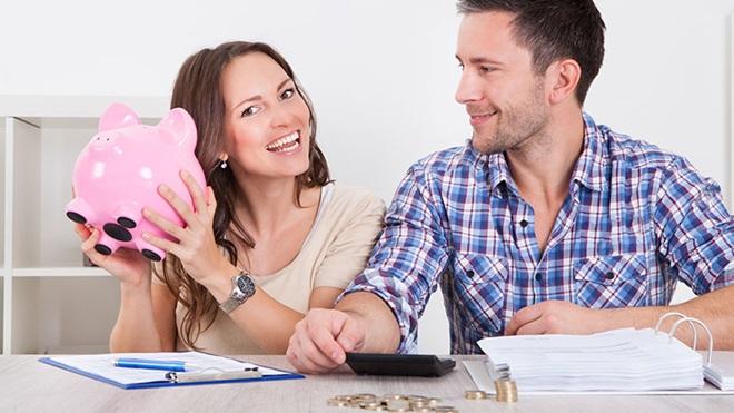 casal a fazer contas a orçamento com um porquinho mealheiro na mão