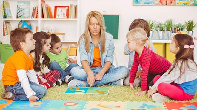 mulher a ler um livro a um grupo de crianças