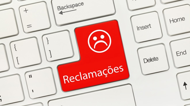 tecla enter do computador com uma cara triste e a palavra reclamações escrita