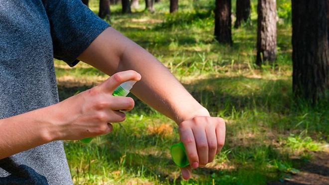 pessoa a aplicar repelente no braço