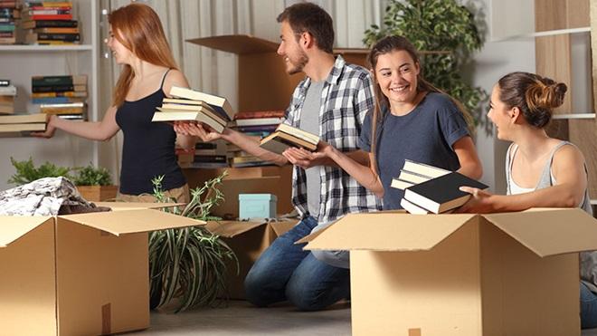 estudantes à procura de alojamento arrumam livros na sala