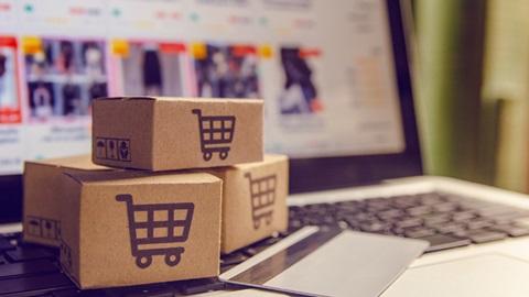 pequenas caixas de papel com símbolos de carrinhos de compras em cima do computador e com um cartão Deco Mais