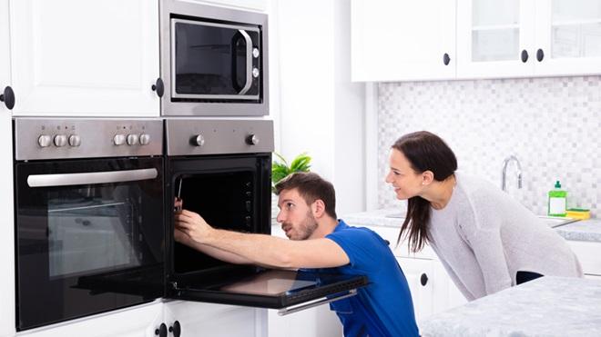 Pessoa na cozinha a tentar reparar um forno